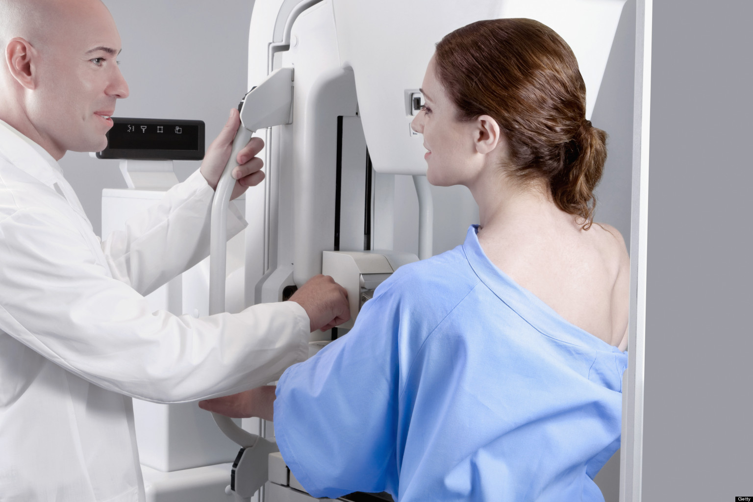 Doctor assisting a female patient for mammogram