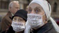 In this photo taken on Friday, May 6, 2016 women wear masks that read 'Corruption Kills' during a protest joined by hundreds against irregularities in the country's health system. Prosecutors searched the Hexi Pharma offices, a drugs company which authorities say has supplied dozens of hospitals with sub-standard disinfectant, and the home of the company owner Saturday, May 7, while police officers took away documents and samples from 25 hospitals in Bucharest and around the country that were affected by the issue. (AP Photo/Vadim Ghirda)